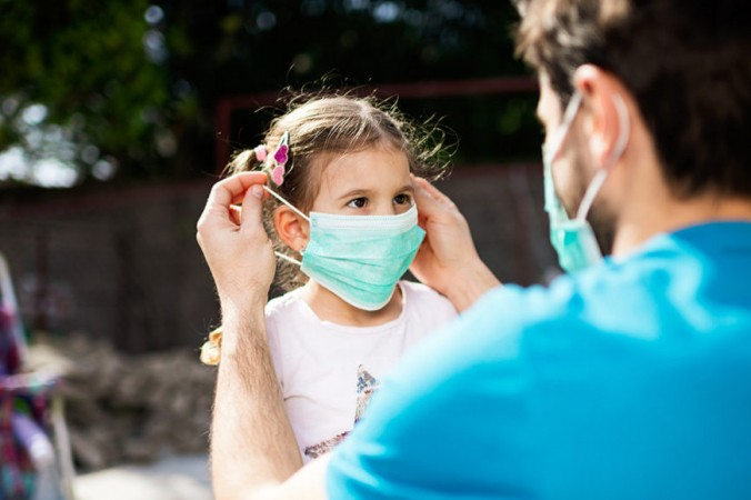 Взрослый надевает медицинскую маску девочке. SanyaSM/E+/Getty Images | Epoch Times Россия