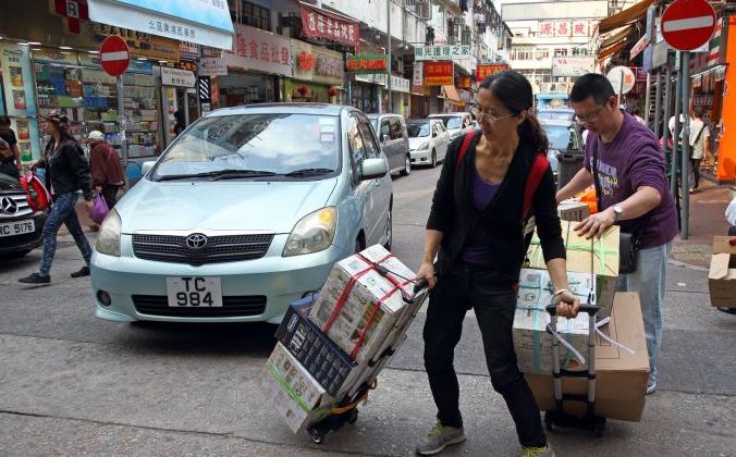 Двое жителей материка везут свои товары на тележках, идущих через улицу Шеунг Шуй, Северный округ Гонконга, 12 апреля 2015 г. (Epoch Times) | Epoch Times Россия