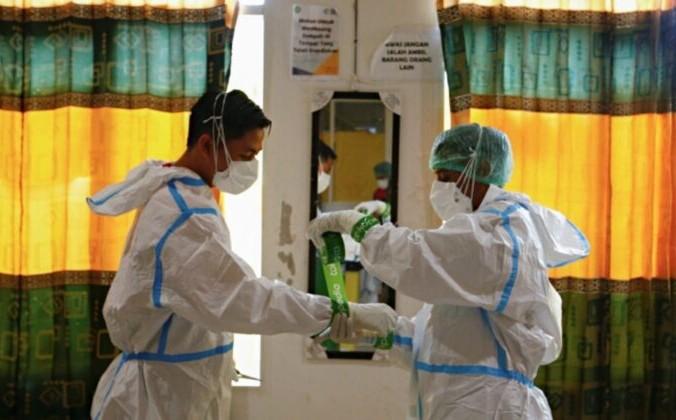 Медицинские работники в СИЗ (средствах индивидуальной защиты) готовятся к лечению пациентов в больнице с COVID-19 в Джакарте, Индонезия, 17 июня 2021 г. | Epoch Times Россия