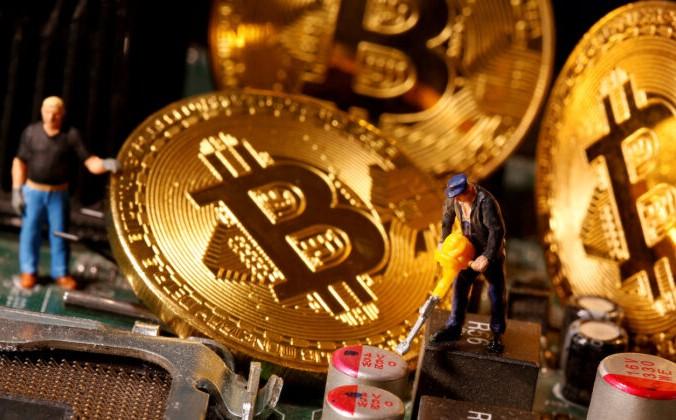 Изображение виртуальной валюты биткоин и маленькие игрушечные фигурки размещены на материнской плате компьютера на этой иллюстрации, сделанной 7 января 2021 г. Dado Ruvic / Reuters   Epoch Times Россия