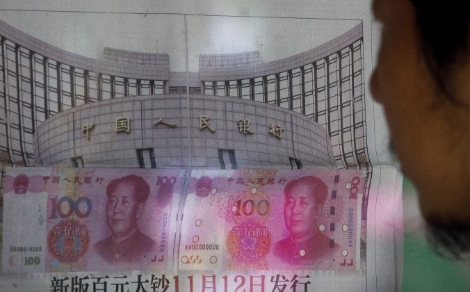 Мужчина читает газетное сообщение о том, что центральный банк Китая объявил о девальвации жестко контролируемой валюты Китая 11 августа 2015 года после спада в торговле, что спровоцировало крупнейшее однодневное падение юаня за десятилетие. (AP Photo / Энди Вонг) | Epoch Times Россия