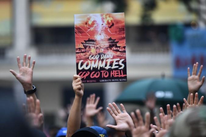 Протестующий держит плакат с надписью «Проклятые коммуняки, КПК (Коммунистическая партия Китая) иди в ад» на митинге в районе Ванчай в Гонконге 1 октября 2019 года. ANTHONY WALLACE/AFP via Getty Images | Epoch Times Россия