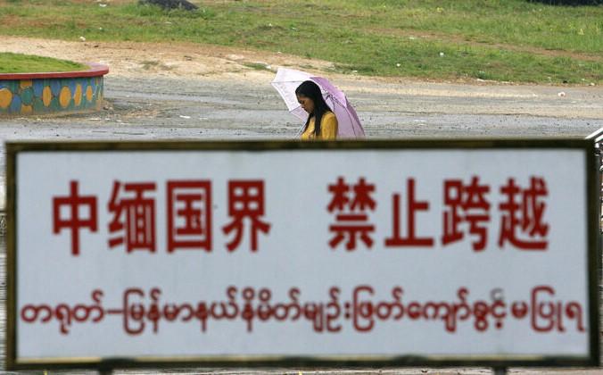 Бирманская женщина идёт за предупреждающим знаком вдоль линии границы в китайско-бирманском пограничном городе Вандинг, в юго-западной провинции Китая, Юньнань, 27 сентября 2007 г. Фото: STR / AFP через Getty Images | Epoch Times Россия