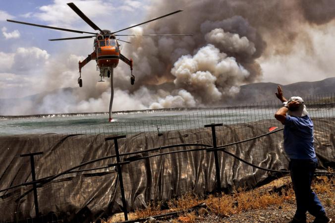 Вертолёт наполняют водой изрезервуара вовремя пожара возле деревни Спатховуни, недалеко отКоринфа, Греция, 23июля 2021г. (Vassilis Psomas / Reuters) | Epoch Times Россия