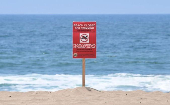 Знак указывает на то, что пляж штата Доквейлер закрыт для купания после разлива сточных вод в Плайя-дель-Рей в округе Лос-Анджелес 13 июля 2021 г. Frederic J. Brown/AFP Via Getty Images | Epoch Times Россия