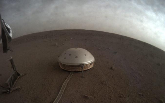 Облака дрейфуют над куполообразным сейсмометром SEIS спускаемого аппарата InSight на поверхности Марса, 22 июля 2021 г. NASA / JPL-Caltech через AP   Epoch Times Россия