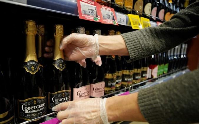 Сотрудник расставляет бутылки российского «игристого вина» в супермаркете в Москве 5 июля 2021 г. Tatyana Makeyeva/Reuters | Epoch Times Россия