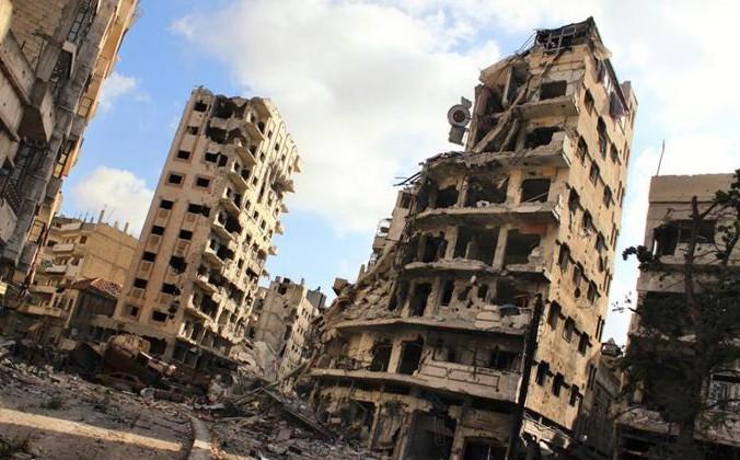 Здания, повреждённые в результате авиаударов и обстрелов сирийского правительства, в районе Джурет аль-Чия в Хомсе, Сирия, 3 июля 2013 г. Lens Young Homsi/AP Photo | Epoch Times Россия