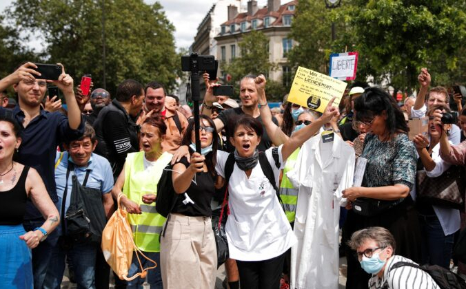 Протестующие держат плакаты и транспаранты во время демонстрации против ограничений из-за COVID-19 в Париже 24 июля 2021 г. Benoit Tessier / Reuters | Epoch Times Россия