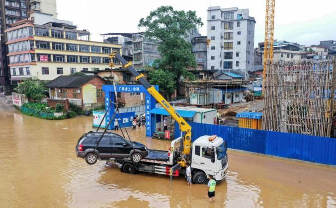 Кран поднимает автомобиль на затопленной улице возле реки Жунцзян после проливных дождей в Ронгане, в южном регионе Китая Гуанси, 2 июля 2021 года. STR/AFP via Getty Images | Epoch Times Россия