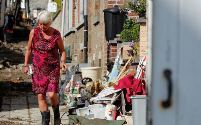 Женщина идёт по местности, пострадавшей от проливных дождей в Динане, Бельгия, 25 июля 2021 г. | Epoch Times Россия