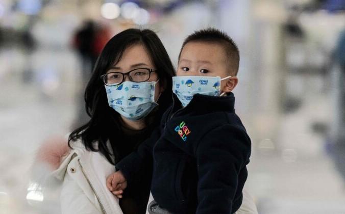 Женщина c ребёнком идёт к стойкам регистрации в международном аэропорту Дасин в Пекине 21 января 2020 г. Nicolas Asfouri/AFP via Getty Images | Epoch Times Россия