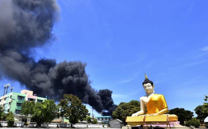 Поднимающийся дым виден за гигантской статуей Будды в провинции Самутпракан, Таиланд, 5 июля 2021 года. AP Photo   Epoch Times Россия
