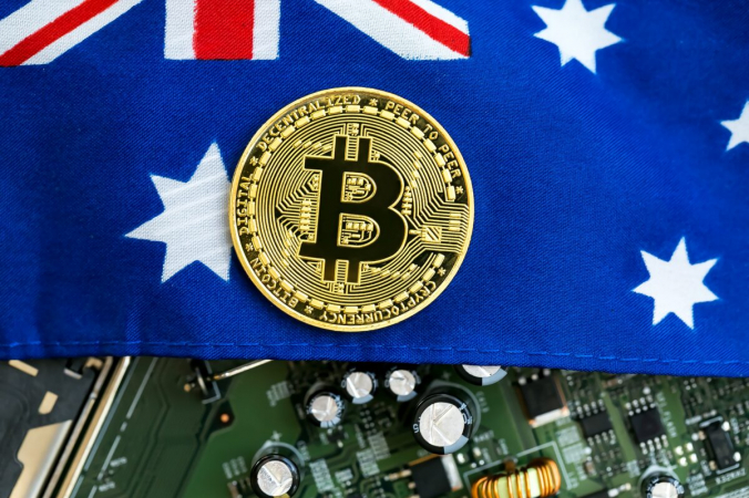Символ криптовалюты биткойн над австралийским флагом и электронными компонентами. (Tierney / Adobe Stock)   Epoch Times Россия