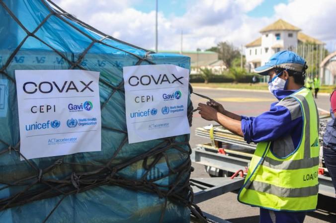 Рабочий обрабатывает коробки свакцинами Oxford / AstraZeneca COVID-19 вмеждународном аэропорту Ивато вАнтананариву, Мадагаскар, 8мая 2021 года. (Mamyrael/AFP via Getty Images)   Epoch Times Россия