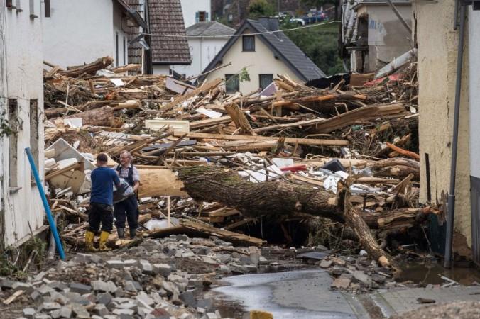 Двое мужчин убираются рядом с обломками домов, разрушенных наводнением в Шульде недалеко от Бад-Нойенара, западная Германия, 15 июля 2021 года. BERND LAUTER/AFP via Getty Images | Epoch Times Россия
