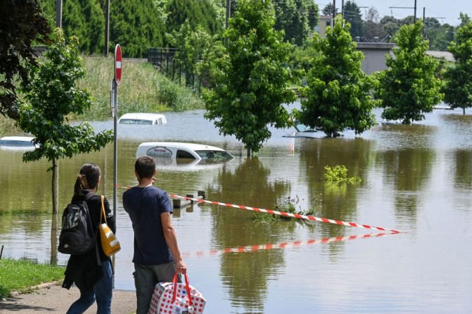 Прохожие смотрят на автомобили затопленной территории после проливного дождя, выпавшего в последние несколько дней, в Лоухане, на севере Франции, 17 июля 2021 года. PHILIPPE DESMAZES/AFP via Getty Images | Epoch Times Россия