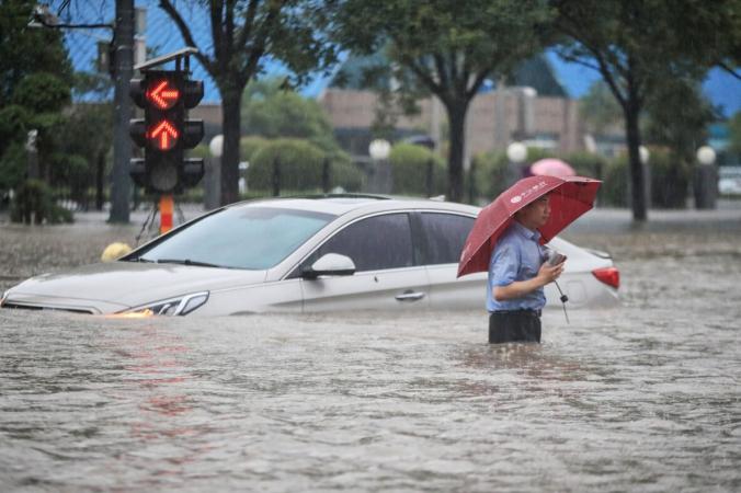 Мужчина пробирается мимо затонувшего автомобиля по затопленной улице после проливных дождей в Чжэнчжоу, провинция Хэнань в центральном Китае, 20 июля 2021 года. (STR/AFP via Getty Images) | Epoch Times Россия