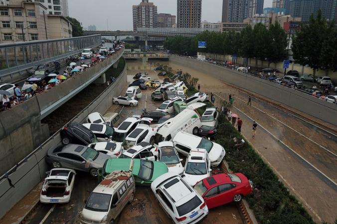 Вид с высоты птичьего полета показывает автомобили, стоящие в паводковых водах у входа в туннель после сильных дождей, обрушившихся на город Чжэнчжоу, провинция Хэнань в центральном Китае, 22 июля 2021 года. NOEL CELIS/AFP via Getty Images | Epoch Times Россия