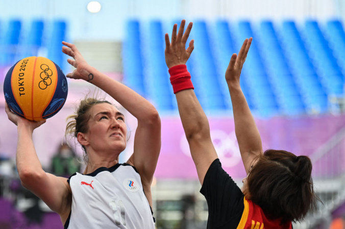 Россиянка Анастасия Логунова (слева) борется за мяч с китайкой Ван Лили на Олимпиаде в Токио, 24 июля 2021 года. Фото: by ANDREY ISAKOVICH / AFP via Getty Images   Epoch Times Россия