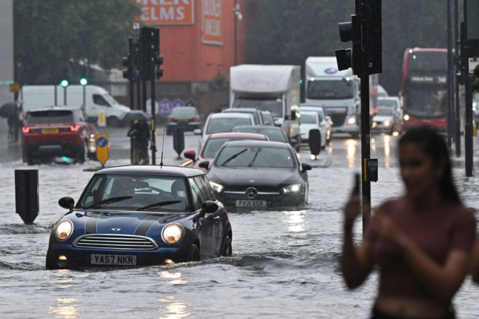 Автомобили едут по затопленной дороге в лондонском районе Девять вязов 25 июля 2021 года во время сильного дождя. JUSTIN TALLIS/AFP via Getty Images | Epoch Times Россия