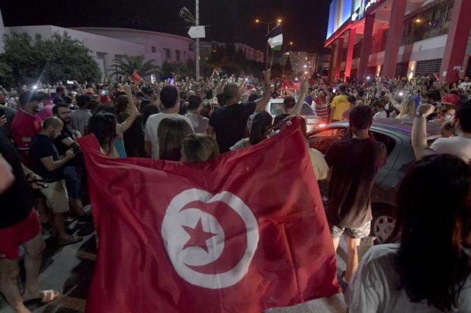 Люди радуются объявлению президентом Туниса Кайса Саида о роспуске парламента и увольнении премьер-министра Хичема Мечичи после дня общенациональных протестов в Тунисе 25 июля 2021 года. FETHI BELAID/AFP via Getty Images | Epoch Times Россия