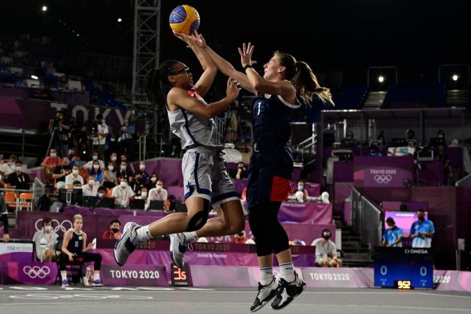 Американка Аллиша Грей (слева) прыгает, чтобы передать мяч во время финального матча по баскетболу 3х3 среди женщин между сборными США и России в парке городского спорта Аоми в Токио 28 июля 2021 года. Фото: by JAVIER SORIANO/AFP via Getty Images | Epoch Times Россия