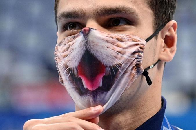 Золотой призёр Евгений Рылов поправляет маску после финала заплыва на 200 метров на спине среди мужчин во время Олимпиады-2020 в Токио, 30 июля 2021 г. OLI SCARFF/AFP via Getty Images | Epoch Times Россия