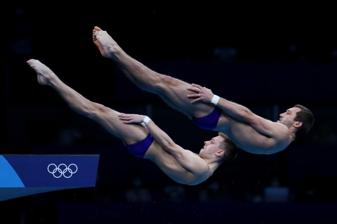 Александр Бондарь и Виктор Минибаев в финале соревнований по синхронным прыжкам в воду с 10-метровой вышки на Олимпийских играх 2020 года в Токио. Фото: Al Bello/Getty Images | Epoch Times Россия