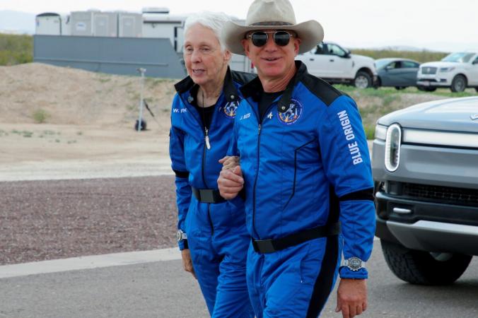 Американский бизнесмен-миллиардер Джефф Безос идет с напарником Уолли Фанком по посадочной площадке после того, как они совершили первый полет Blue Origin к краю космоса в соседнем городе Ван-Хорн, штат Техас, США, 20 июля 2021 года (Джо Шкипер / Рейтер) | Epoch Times Россия