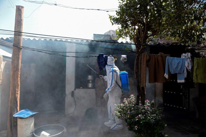 Медицинский работник распыляет дезинфицирующее средство возле дома в качестве меры предосторожности против птичьего гриппа в районе Сола, на окраине Ахмедабада, Индия, 5 марта 2021 г. (Sam Panthaky/AFP via Getty Images)   Epoch Times Россия
