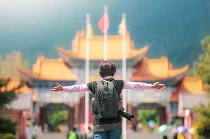 Туристка перед храмом Чуншен в старом городе Дали, Юньнань, Китай. (Изображение: <a href=