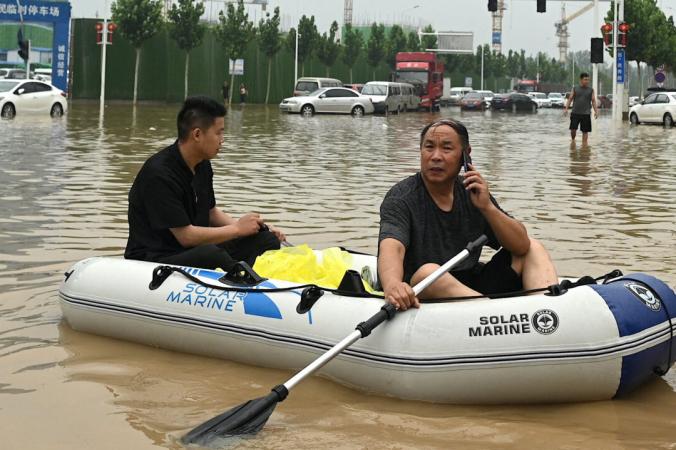 Люди используют резиновую лодку, чтобы пересечь затопленную улицу после наводнения, унесшего жизни не менее 33 человек в начале недели в городе Чжэнчжоу в китайской провинции Хэнань. 23 июля 2021 года. (Noel Celis/AFP via Getty Images)   Epoch Times Россия