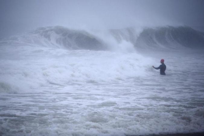 Мэтт Прю из Стонингтона, штат Коннектикут, решил покататься на волнах, вызванных тропическим штормом «Генри» в Вестерли, Род-Айленд, 22 августа 2021 г. (Stew Milne / AP Photo)   Epoch Times Россия