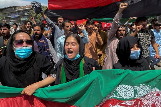 Люди несут национальный флаг на акции протеста в День независимости Афганистана в Кабуле 19 августа 2021 г. (Stringer / Reuters)   Epoch Times Россия