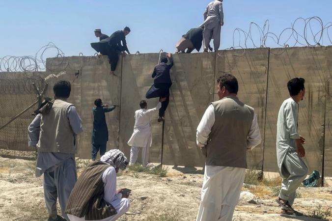 Мужчины пытаются попасть в международный аэропорт имени Хамида Карзая в Кабуле, Афганистан, 16 августа 2021 г. (Stringer / Reuters) | Epoch Times Россия
