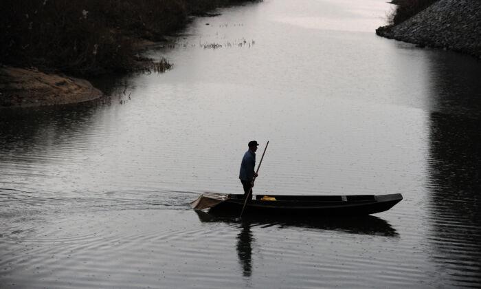 Китайский рыбак плывёт по притоку реки Ялу между Северной Кореей и Китаем 24 ноября 2010 г. (Фредерик Дж. Браун / AFP через Getty Images) | Epoch Times Россия