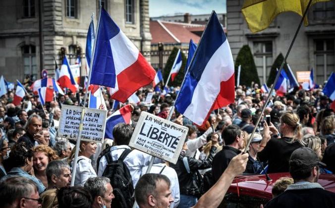 Протестующие во время демонстрации против обязательных пропусков COVID-19 для доступа в общественные места, рядом с Ecole Militaire в Париже, Франция, 7 августа 2021 г. Stephane De Sakutin/AFP | Epoch Times Россия