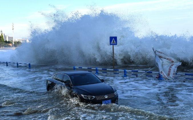 Автомобиль накрыло водой, когда волны от тайфуна «Ин-фа» перекинулись через ограждение в восточной части китайской провинции Шаньдун 25 июля 2021 г. STR / AFP | Epoch Times Россия
