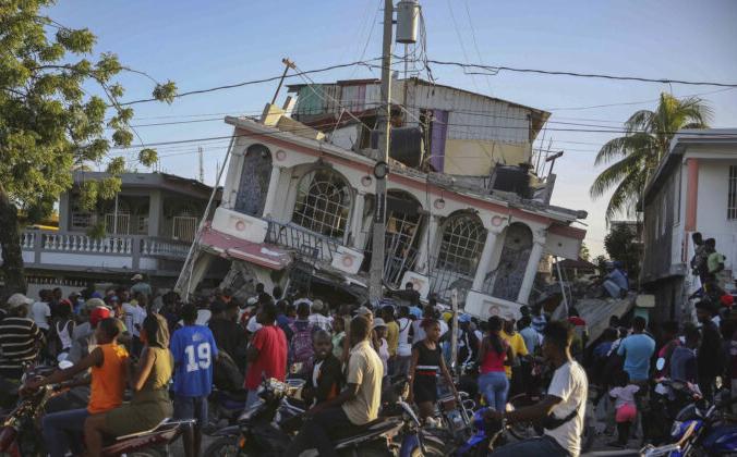 Люди собираются возле отеля Petit Pas, разрушенного землетрясением в Ле-Ке, Гаити, 14 августа 2021 г. Joseph Odelyn / AP Photo | Epoch Times Россия