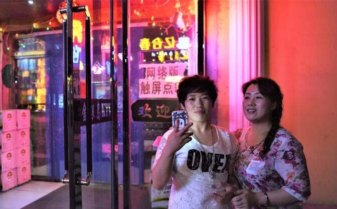 Две женщины у караоке-бара в Хуньчуне, провинция Цзилинь на северо-востоке Китая, 24 июня 2015 г. Greg Baker/AFP via Getty Images | Epoch Times Россия
