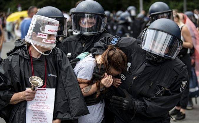 Полиция арестовывает протестующую девушку во время демонстрации против мер по борьбе с COVID-19 у Колонны Победы в Берлине 1 августа 2021 г. Fabian Sommer / dpa via AP   Epoch Times Россия