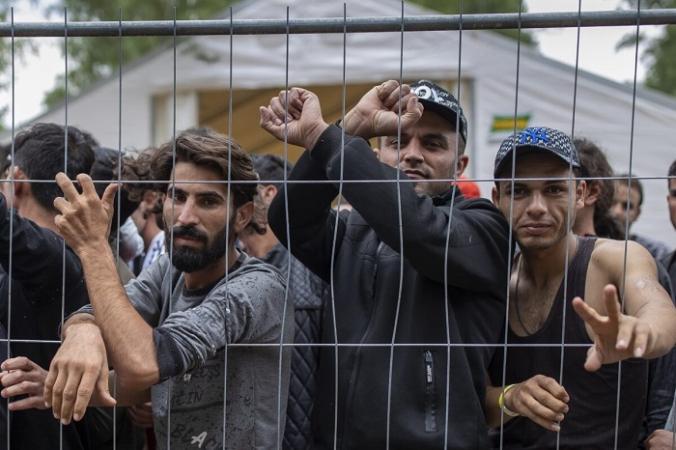 Нелегальные иммигранты стоят за забором внутри недавно построенного лагеря беженцев на военном полигоне Руднинкай, примерно в 38 км к югу от Вильнюса, Литва, 4 августа 2021 г. (Mindaugas Kulbis/AP Photo) | Epoch Times Россия