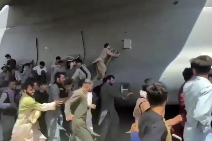 Сотни людей бегут рядом с транспортным самолётом C-17 ВВС США, некоторые забираются на самолёт, когда он движется по взлётно-посадочной полосе международного аэропорта в Кабуле, Афганистан, 16 августа 2021 г. (Verified UGC via AP) | Epoch Times Россия