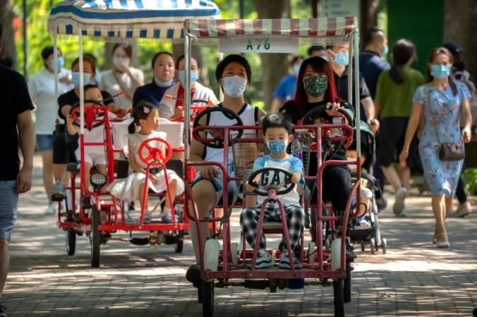Взрослые и дети катаются на велосипедах с педалями в общественном парке в Пекине 21 августа 2021 года. (AP Photo/Mark Schiefelbein)   Epoch Times Россия