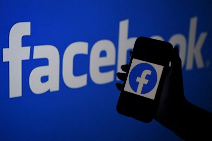 Экран смартфона отображает логотип Facebook на фоне веб-сайта Facebook в Арлингтоне, штат Вирджиния, 7 апреля 2021 г. (Olivier Douliery / AFP via Getty Images) | Epoch Times Россия
