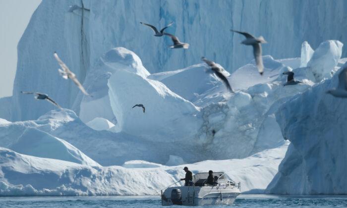 Мужчина ловит рыбу возле айсбергов в ледяном фьорде Илулиссат в западной Гренландии, 4 августа 2019 г. (Шон Гэллап / Getty Images) | Epoch Times Россия