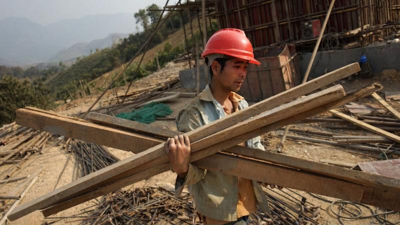 Китайский рабочий несёт материалы для первой железнодорожной линии, соединяющей Китай с Лаосом, в рамках инициативы «Один пояс, один путь» через Меконг в Луангпхабанге, Лаос, 8 февраля 2020 г. (Aidan Jones/AFP via Getty Images) | Epoch Times Россия