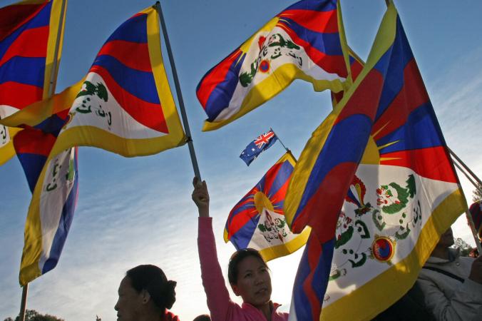 Протибетские протестующие демонстрируют тибетский флаг у здания парламента во время эстафеты Олимпийского огня в Пекине 2008 года через Канберру 24 апреля 2008 года. Torsten Blackwood/AFP via Getty Images | Epoch Times Россия