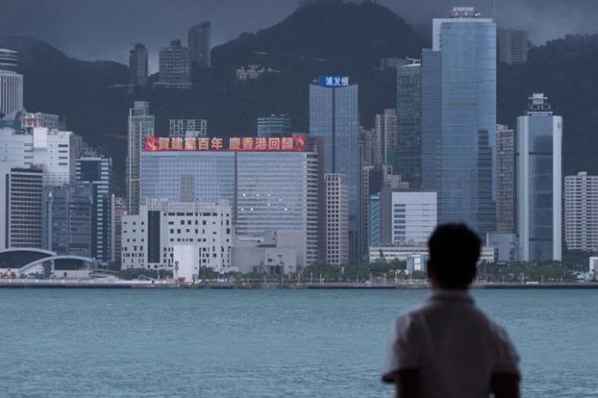 Мужчина смотрит на здание со светодиодным рекламным щитом, посвящённым 100-летию коммунистической партии Китая и 24-й годовщине возвращения Гонконга в Китай. Гонконг, 29 июня 2021 г. (Bertha Wang/AFP via Getty Images) | Epoch Times Россия
